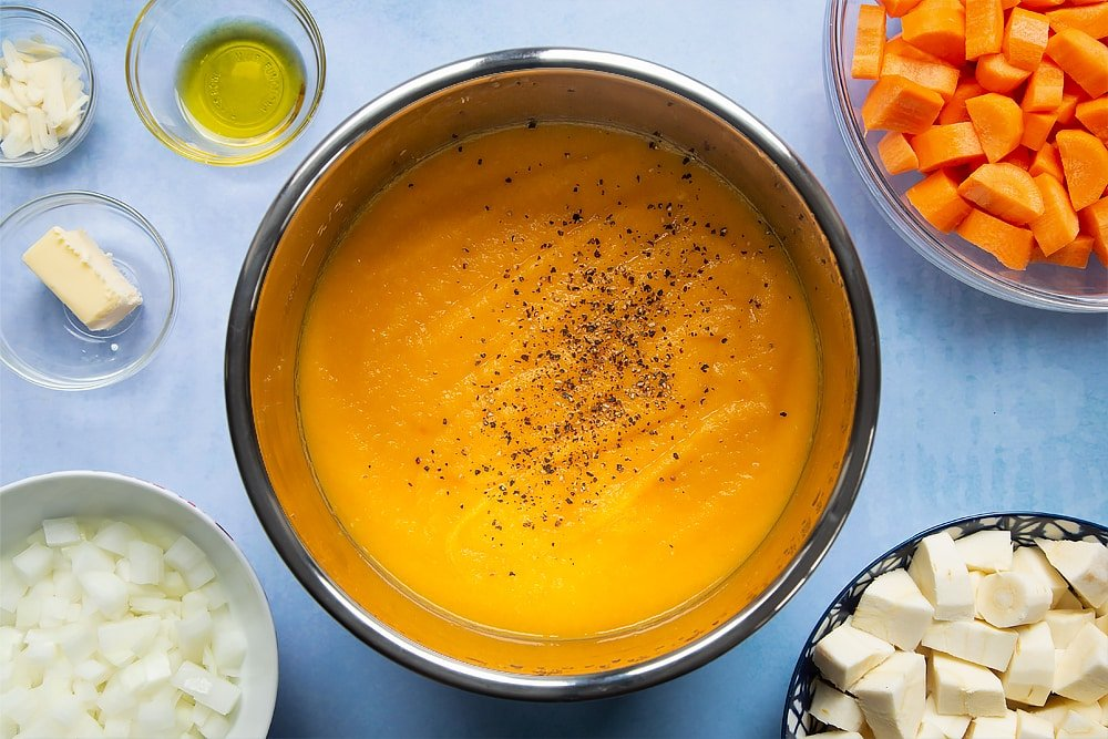 Pan of carrot and parsnip soup with added seasoning. At the side of there's a number of bowls filled with the soups ingredients.