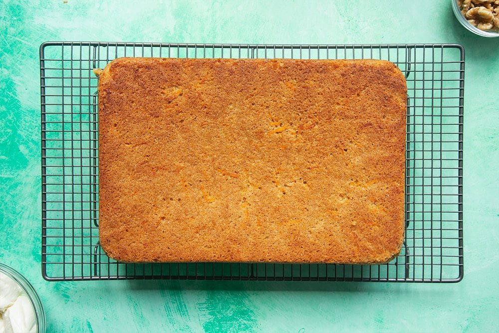 Tipping the carrot cake tray bake out of the cake tin to allow it to thoroughly cool on the wire rack.