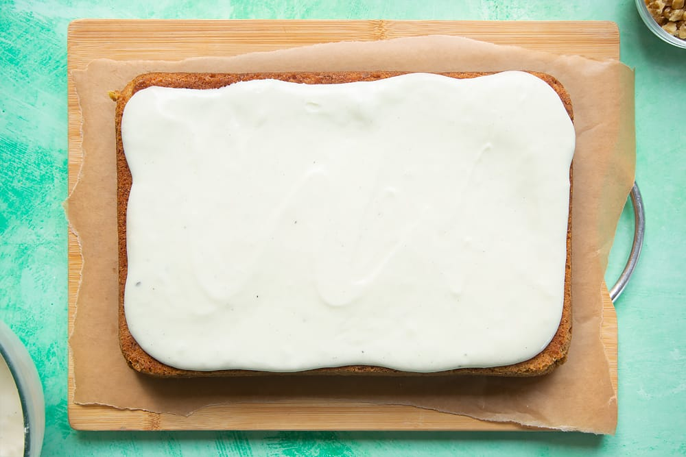 Spreading the creamy frosting over the carrot cake tray bake