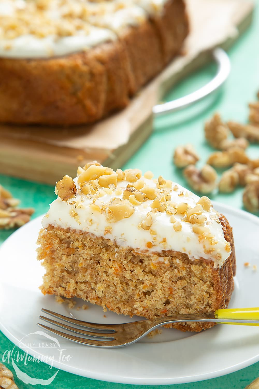 A serving of carrot cake tray bake sliced on a plate with a fork.