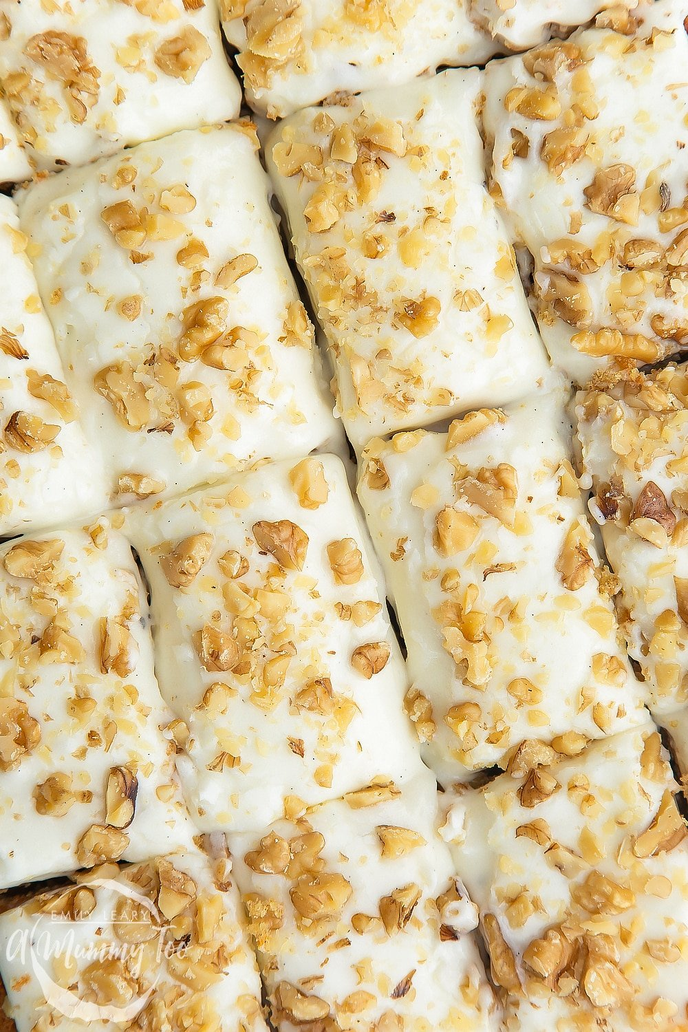 A overhead shot of the carrot cake tray bake which has been cut into serving portions.