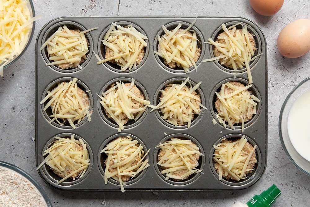 Easy cheese muffin dough in a 12-hole muffin tray. Each is topped with a pinch of cheese. Ingredients to make easy cheese muffins surround the tray.