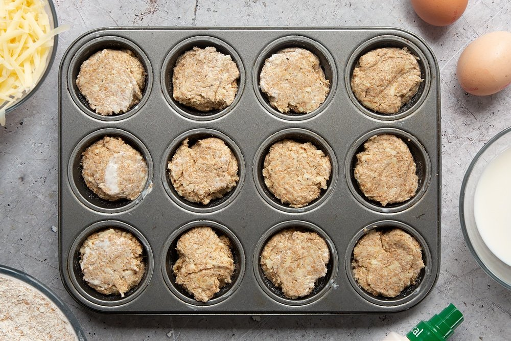 Easy cheese muffin dough in a 12-hole muffin tray. Ingredients to make easy cheese muffins surround the tray.