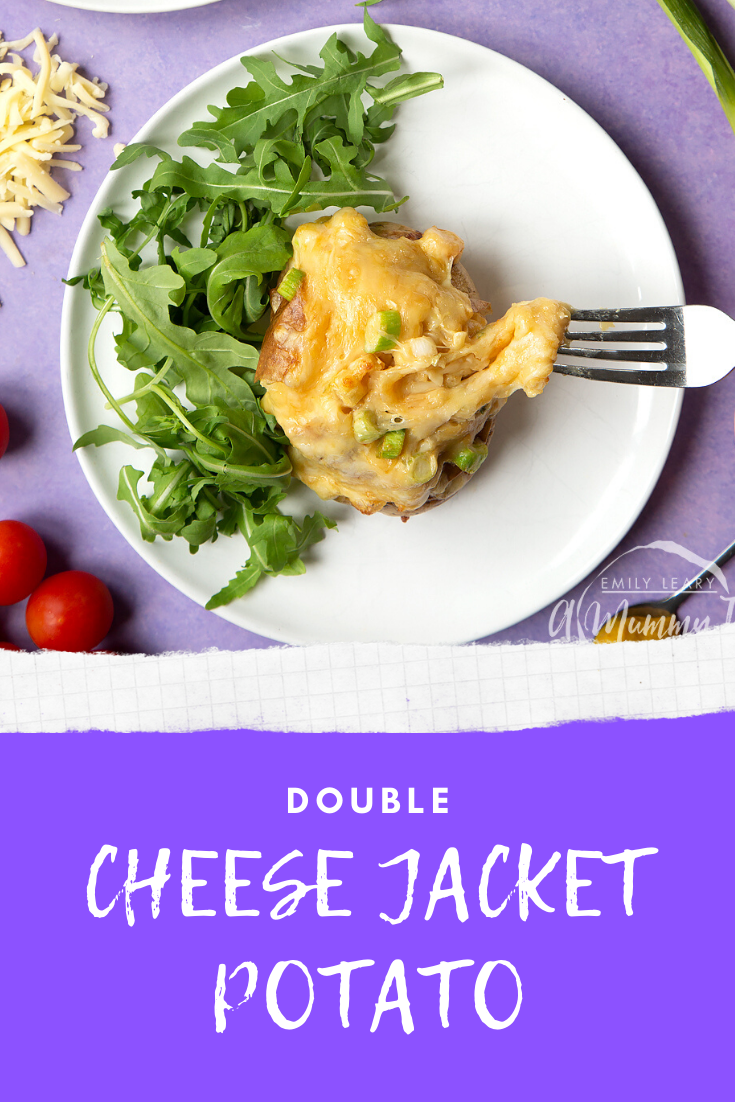 A cheese and onion jacket potato served on a white plate with rocket. Caption reads: double cheese jacket potato