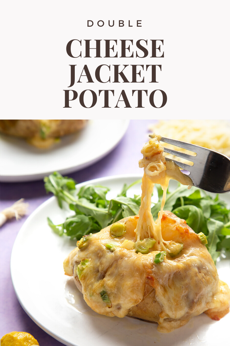 A cheese and onion jacket potato served on a white plate with rocket. A fork lifts the stretchy cheese. Caption reads: double cheese jacket potato