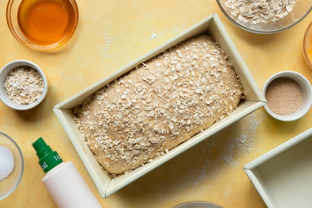 Overhead shot of dough with a sprinkle of oats in a loaf tin