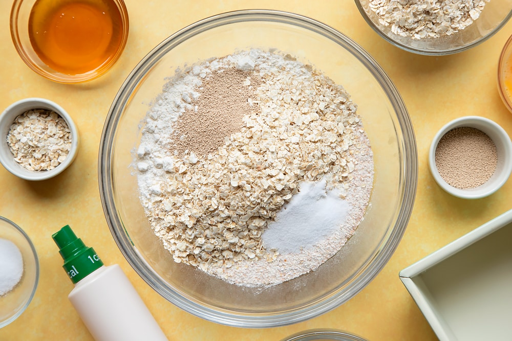 Overhead shot of flour, oats, yeast, and salt in a large clear bowl