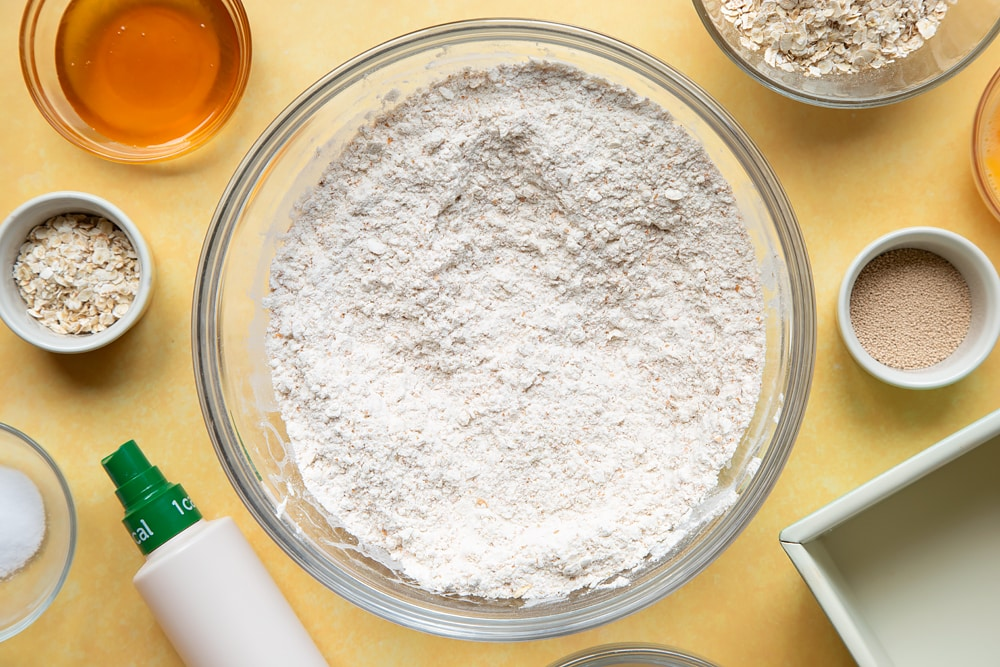 Overhead shot of mixed flour, oats, yeast, and salt in a large clear bowl