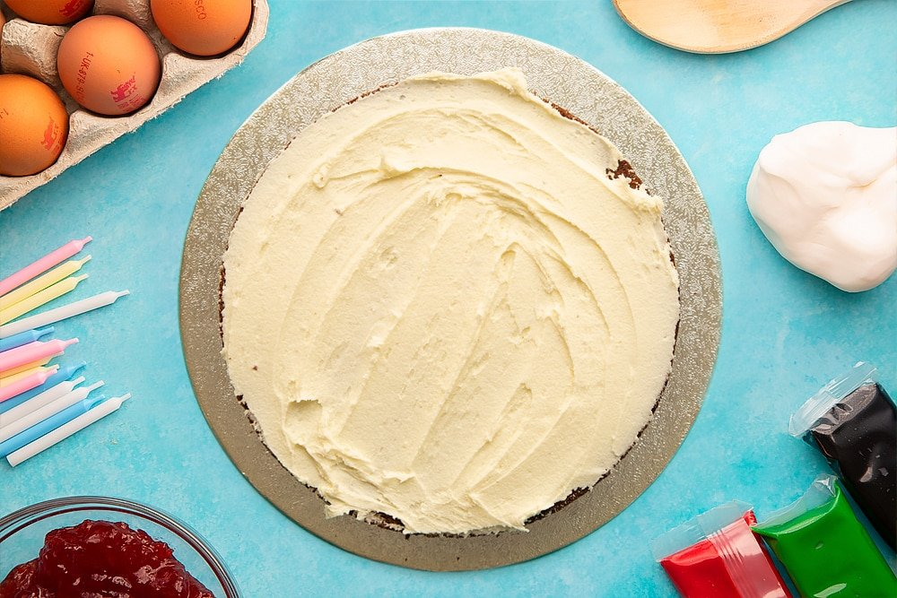 A vanilla sponge spread with buttercream on a round silver cake board. Ingredients to make pizza cake surround the board.