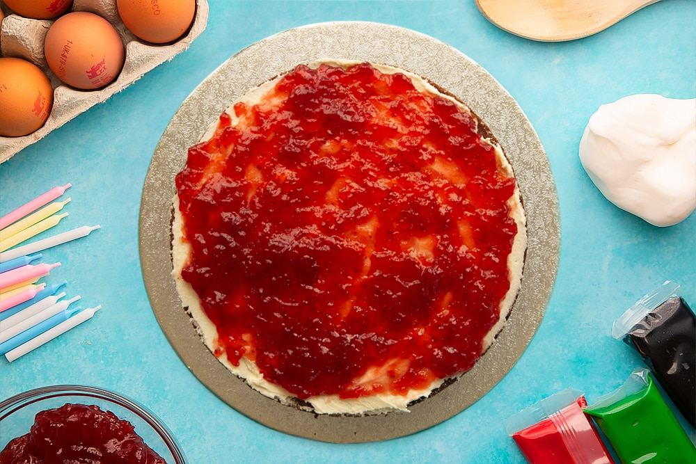A vanilla sponge spread with buttercream and jam on a round silver cake board. Ingredients to make pizza cake surround the board.