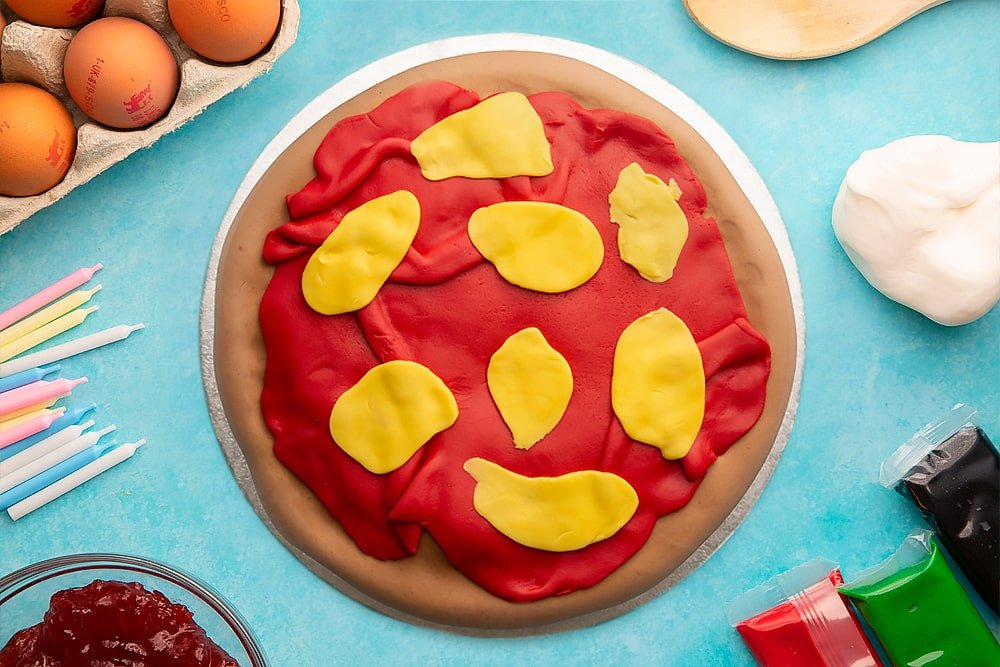 A vanilla sponge sandwich cake covered with brown, red and yellow sugar paste to resemble a pizza on a silver cake board. Ingredients to make pizza cake surround the board.