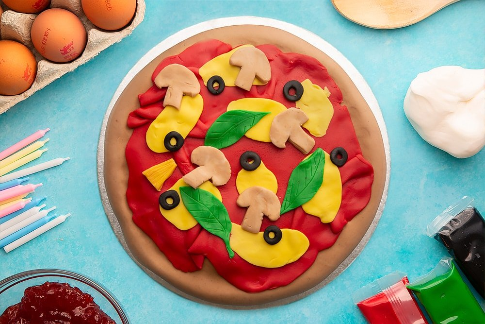 A vanilla sponge sandwich cake covered with brown, red, yellow, black, green and beige sugar paste to resemble a pizza with olives, basil and mushrooms on a silver cake board. Ingredients to make pizza cake surround the board.