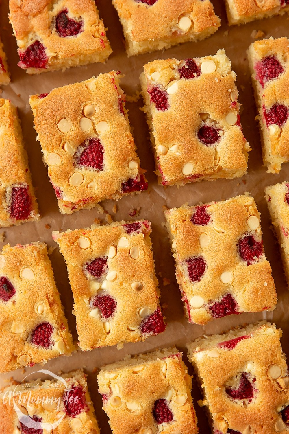 Close up of a raspberry and white chocolate traybake cut into 16 pieces.