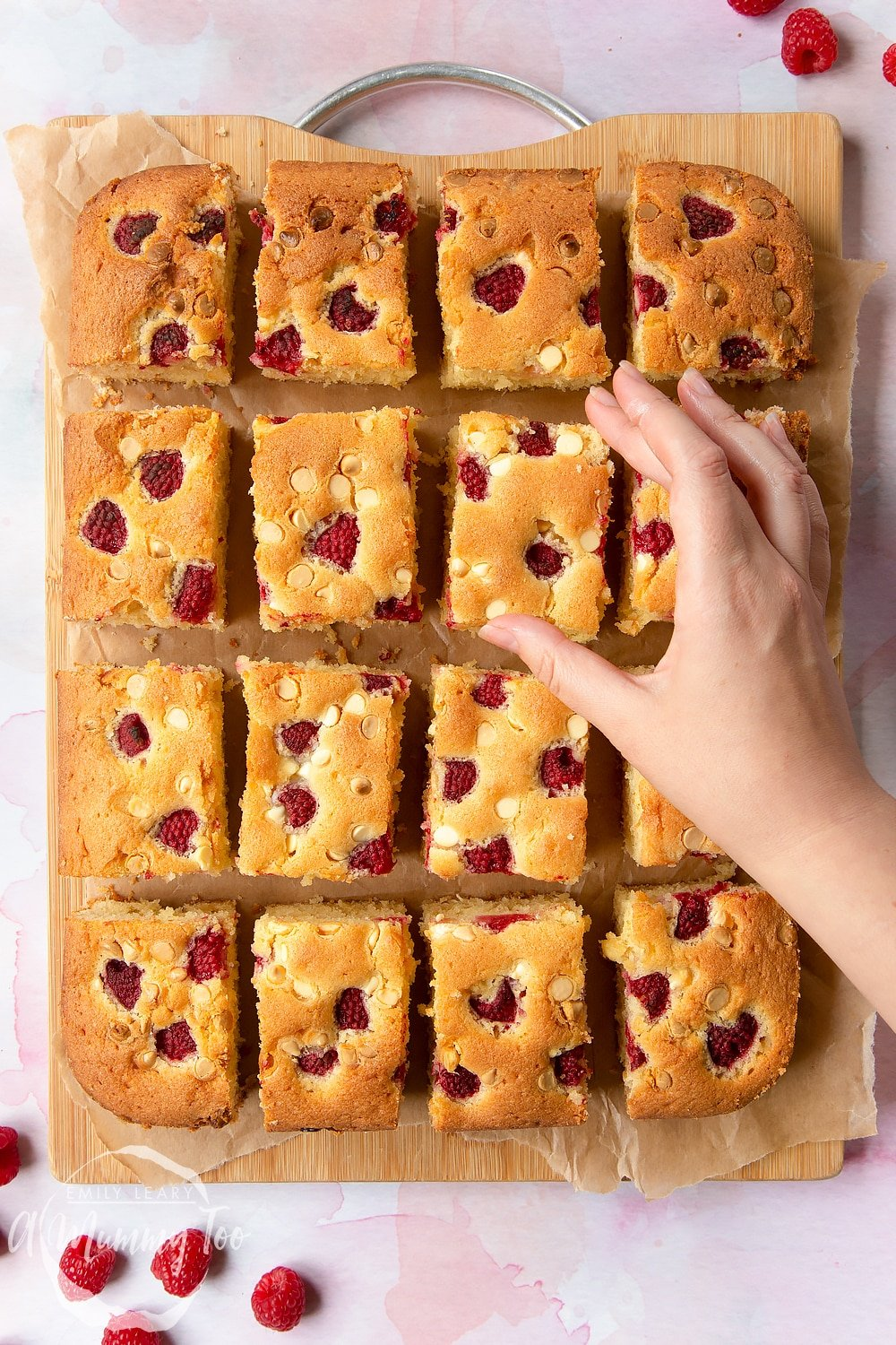 A raspberry and white chocolate traybake cut into servings.