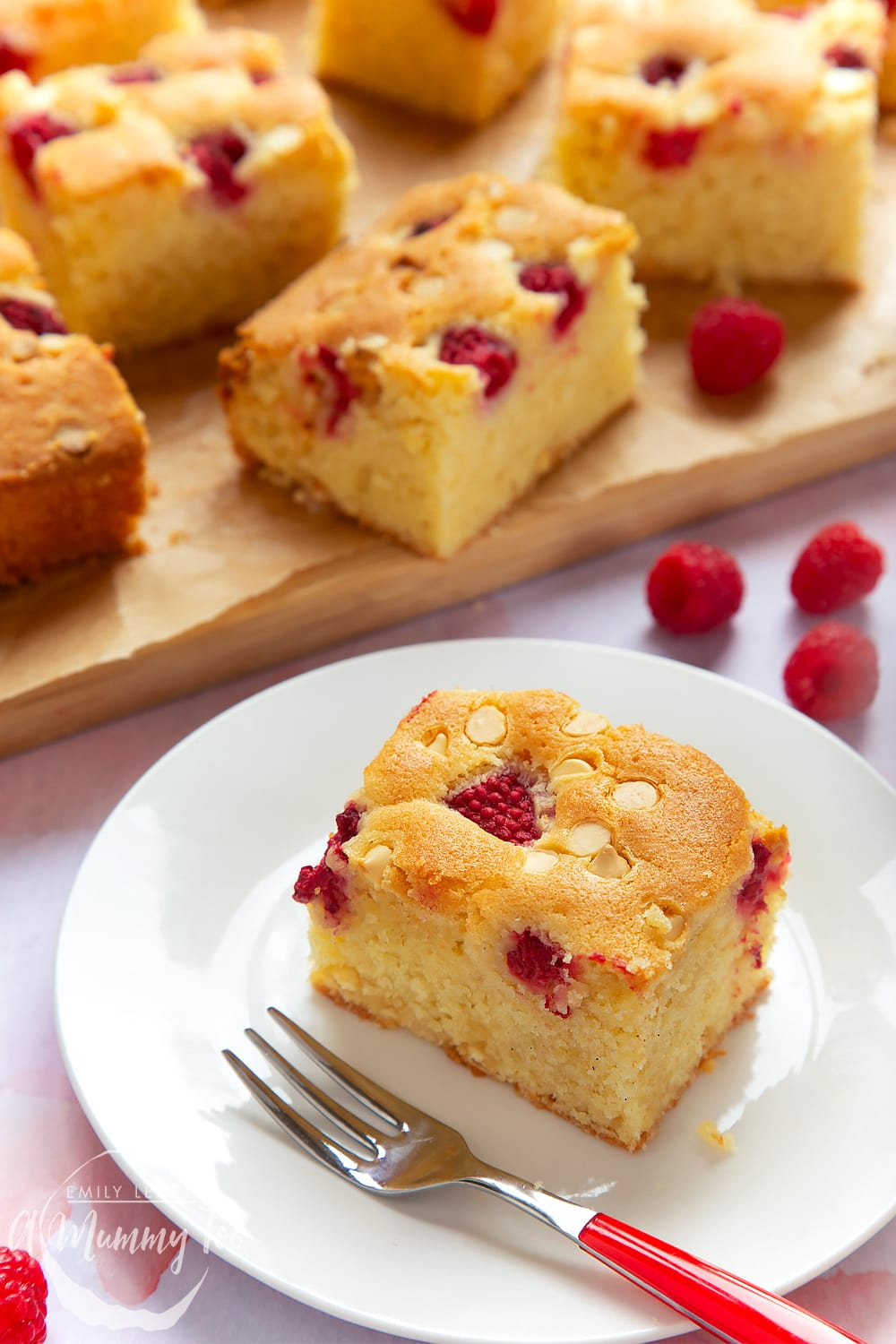 A serving of raspberry and white chocolate traybake on a plate with a fork.