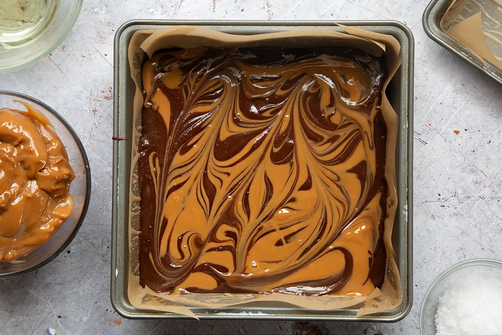 Swirling the mixture with the handle of a spoon to create gooey salted caramel brownies