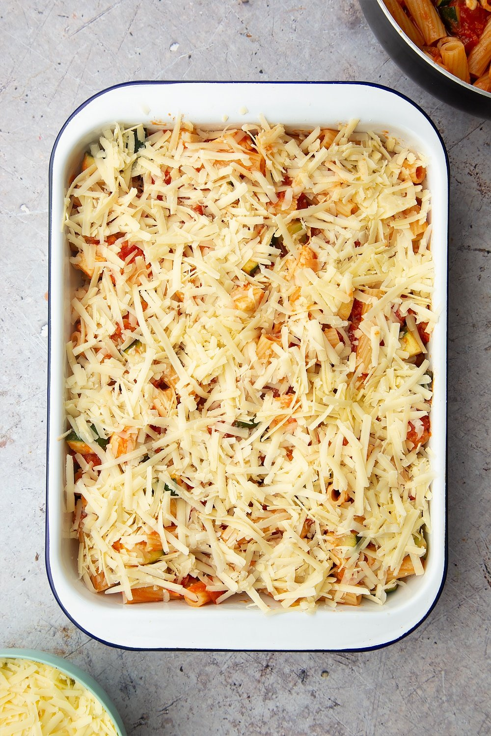 A tray of halloumi pasta bake with grated cheese on the top.