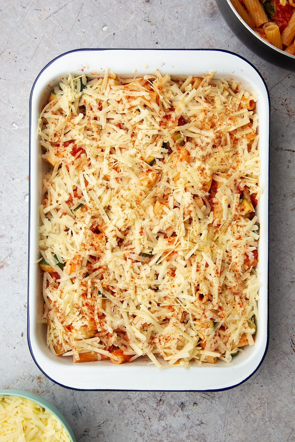 A tray of halloumi pasta bake with a sprinkle of cheese and a dash of smoked paprika on the top ready to be baked in the oven.