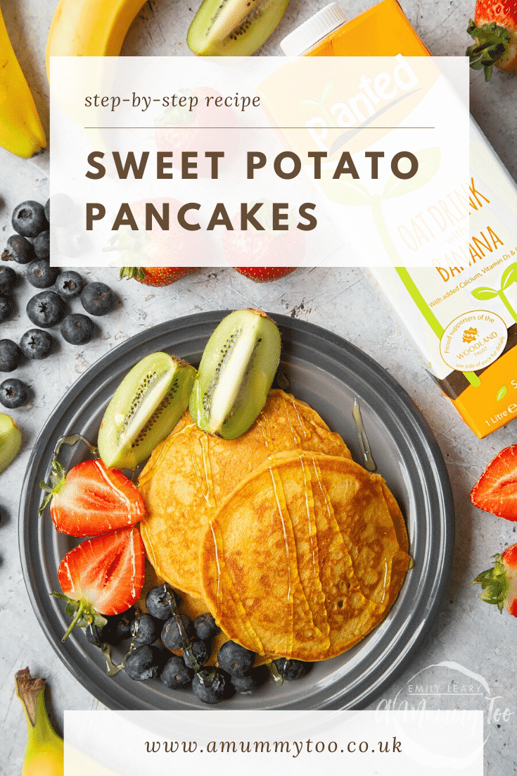 Overhead shot of two sweet potato pancakes on a black plate with a side of fruit in the form of blueberries, chopped strawberries and kiwi. The plate is surrounded by some of the ingredients used to make the pancakes.