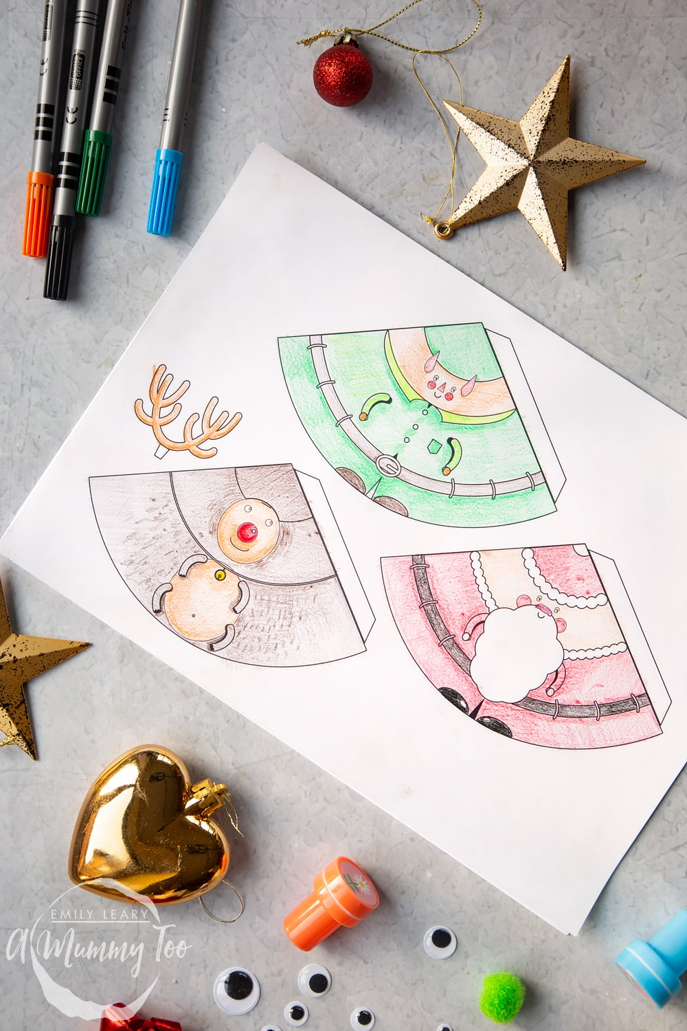 A sheet of A4 paper which has the 3 characters; Santa, elf and reindeer all coloured in with pencils and ready to be cut out and assembled,