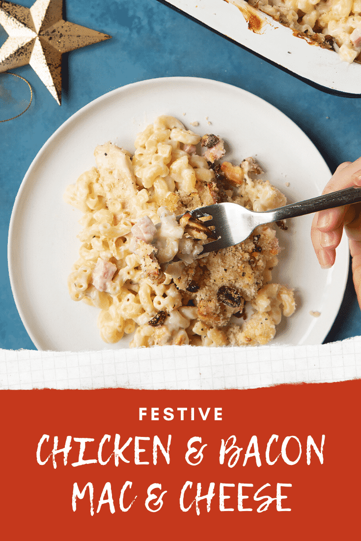 A portion of chicken and bacon mac and cheese served on a small white plate with a fork digging in. A tray containing more of the pasta is shown to one side. Caption reads: festive chicken & bacon mac & cheese