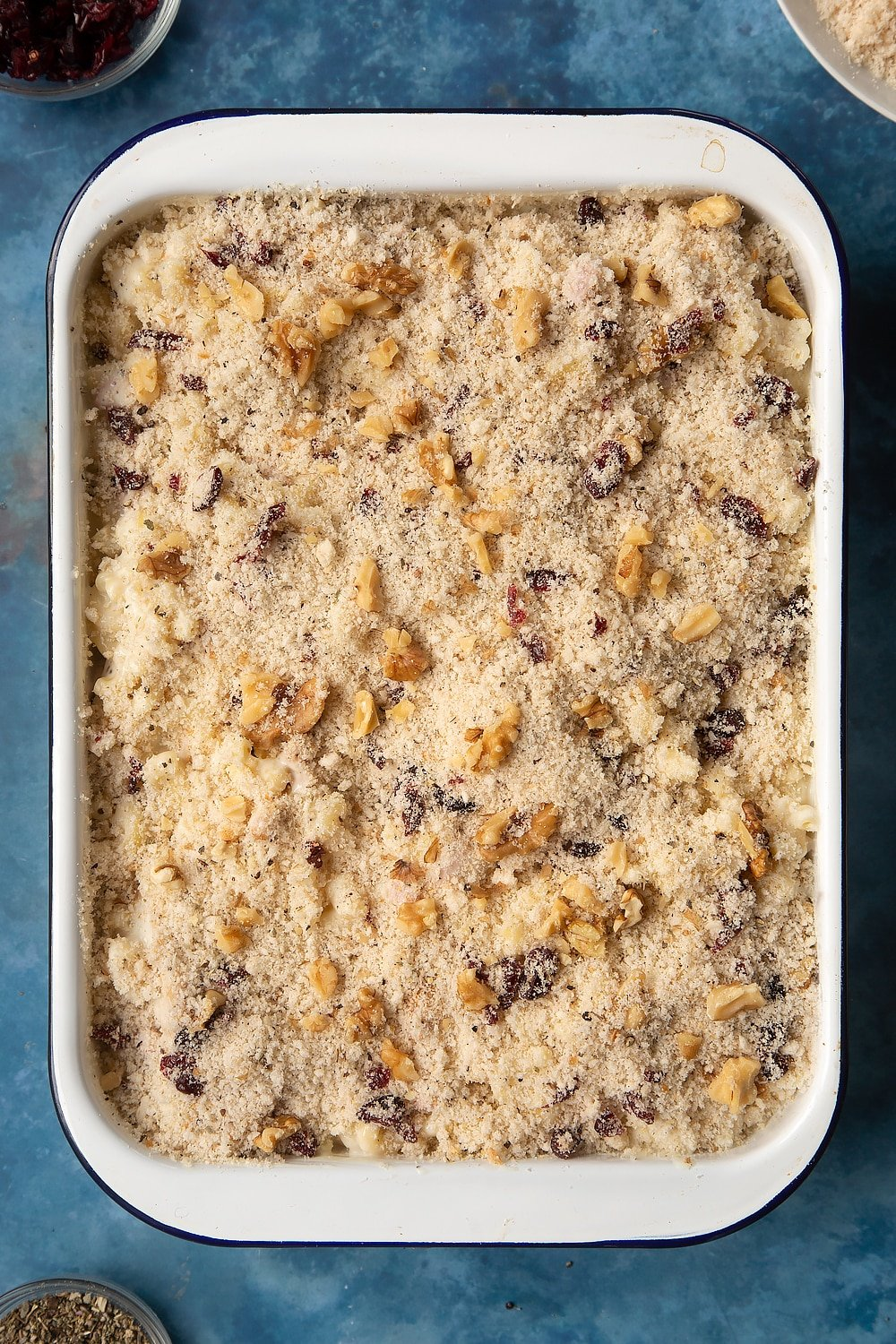 A large roasting pan filled with chicken and bacon mac and cheese, topped with a crumb made from breadcrumbs, dried cranberries, walnuts, garlic granules, dried sage, salt and pepper.