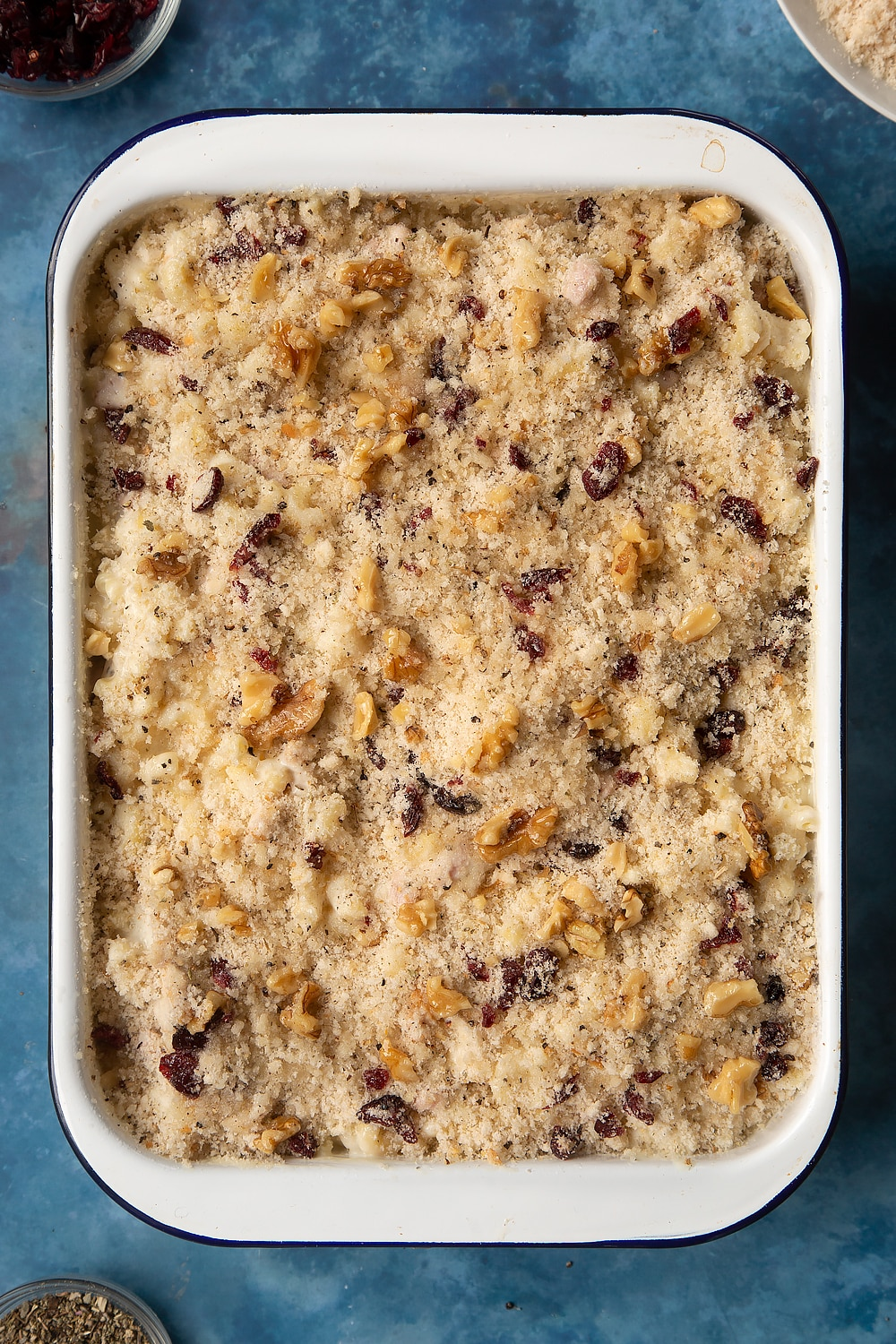A large roasting pan filled with chicken and bacon mac and cheese, topped with a crumb made from breadcrumbs and drizzled with olive oil.
