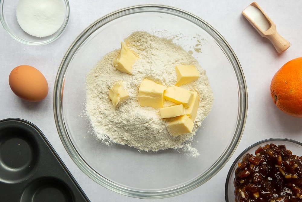Adding flour and butter to a large mixing bowl.