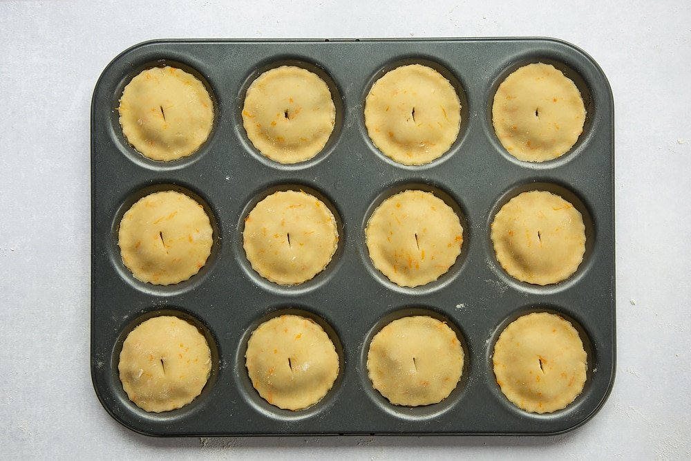 Finished easy mince pies situated in a tin ready to bake with a slit in each which is used to allow the air to breathe through the pie.