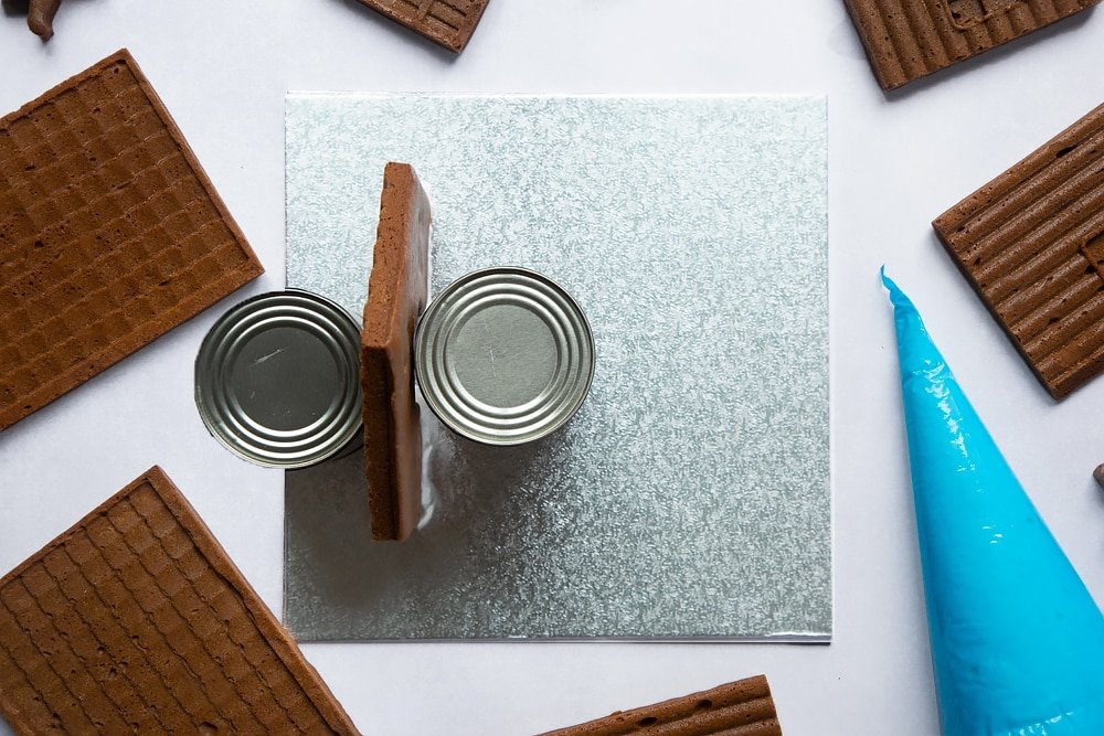 A silver cake board with a piece of gingerbread house wall standing on it. Two cans support the wall on either side.