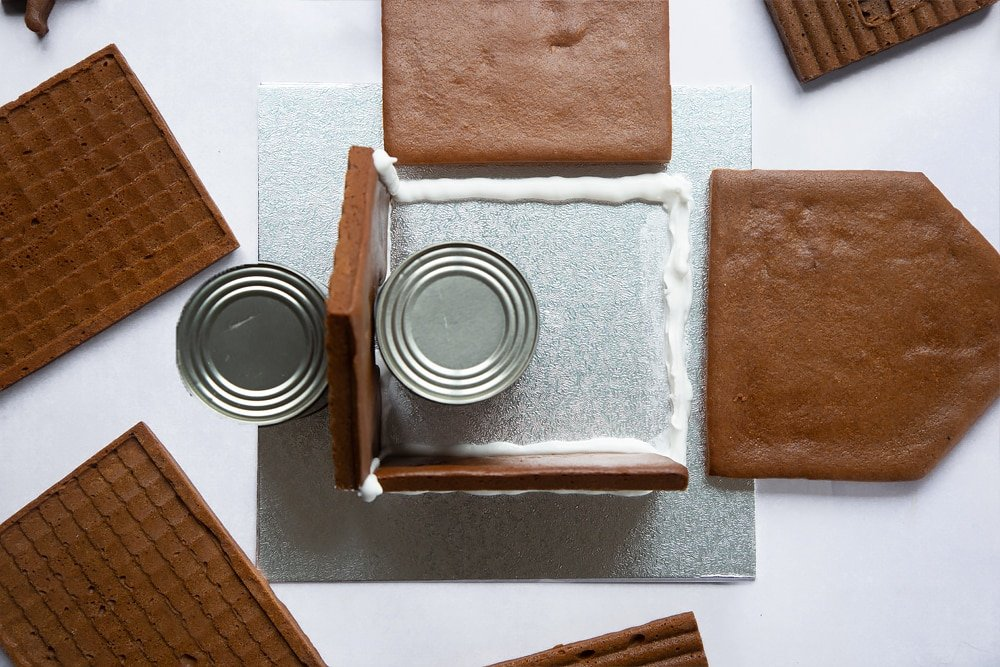A silver cake board with two pieces of gingerbread house wall standing on it. Two cans support one wall on either side. A further line of royal icing is piped where the finals wall will be. they are lying either side of the board.