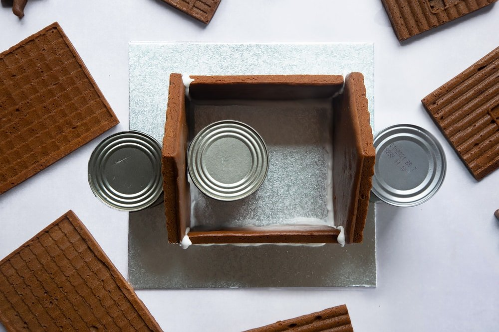 A silver cake board with all four walls of a standing on it. Three cans support the walls.