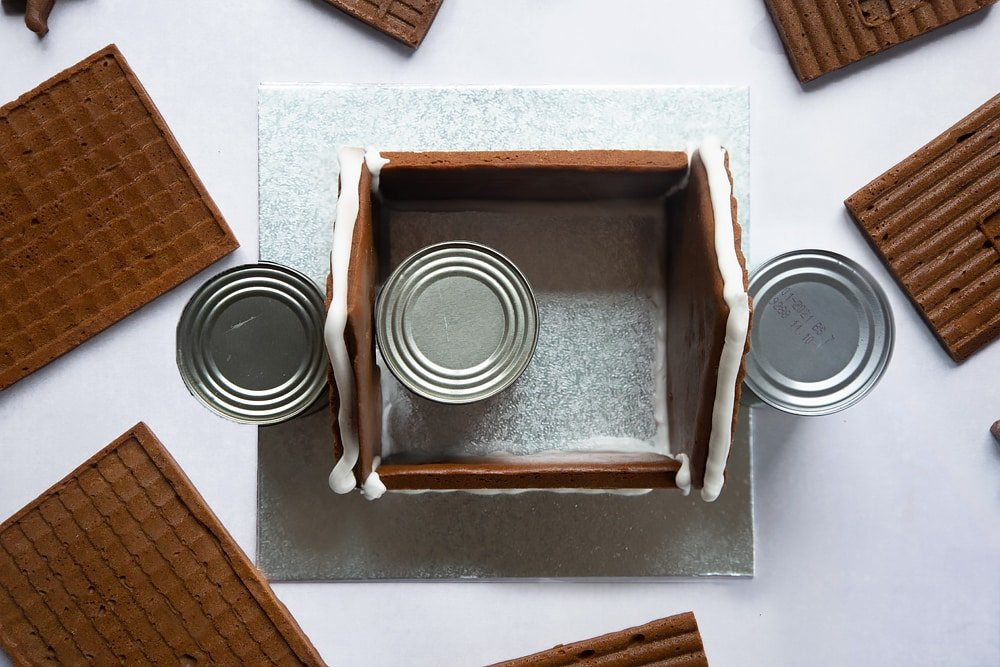 A silver cake board with all four walls of a standing on it. Three cans support the walls. Royal icing is piped along the top where the roof will be added.