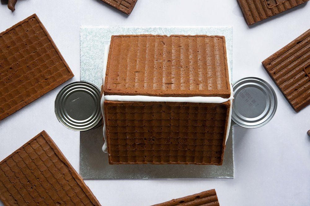 A silver cake board with all four walls of a standing on it and the two roof pieces on top. A line of royal icing is piped along the top where the two roof pieces meet. Two cans support the walls.