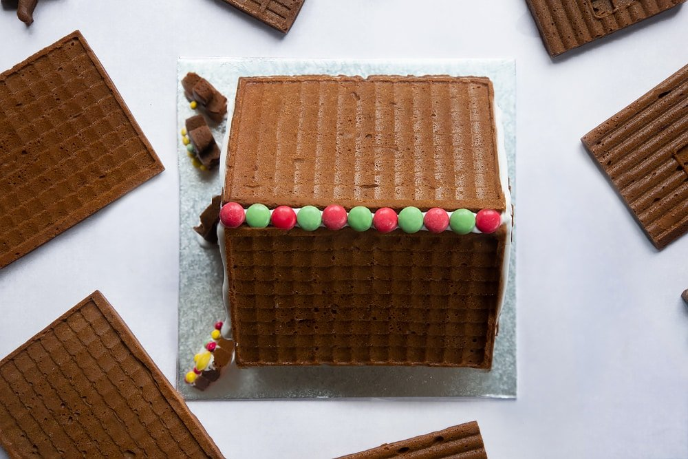 A gingerbread house on a silver board. The top has been decorated with red and green chocolate beans (smarties).