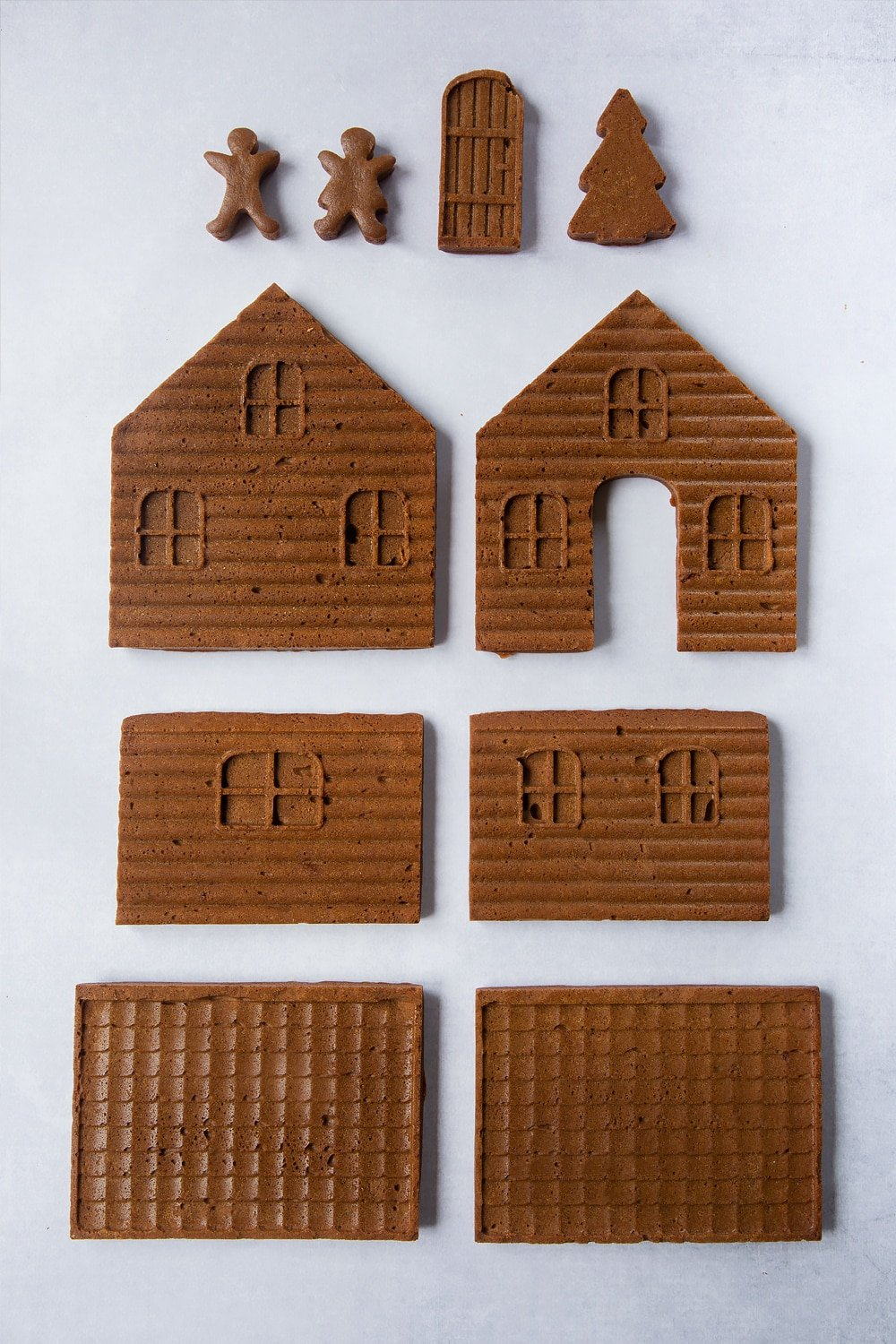 Freshly baked pieces of gingerbread dough, made in a silicone mould so that they form the walls, roof, door, people and Christmas tree to construct into a gingerbread house.