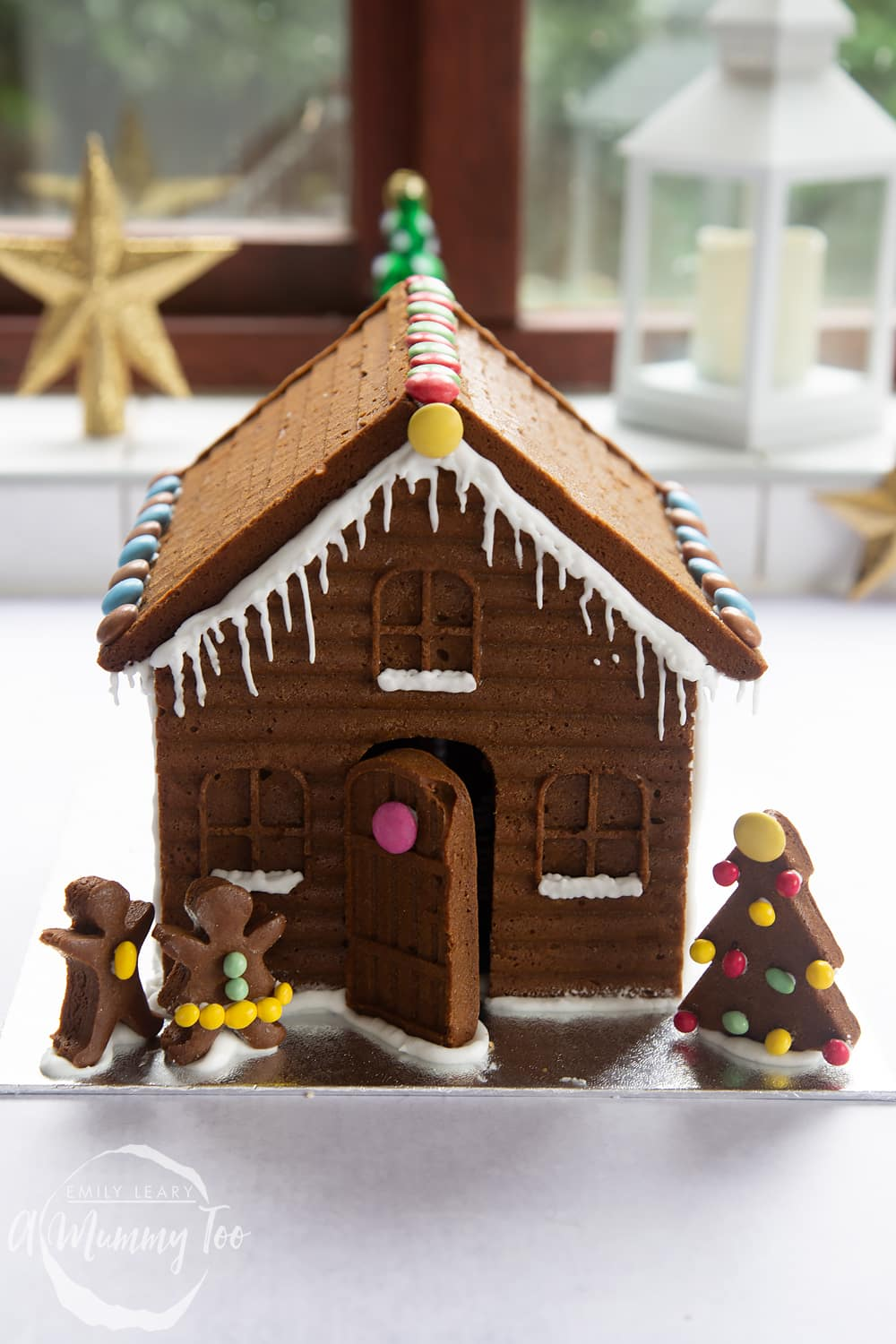 A detailed gingerbread house on a silver board. The house is decorated with smarties and mini chocolate beans. A gingerbread Christmas tree is shown to the left of the house, while two gingerbread people stand to the right.