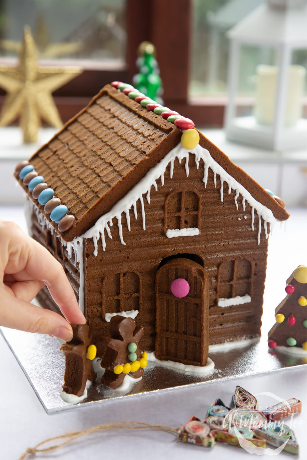 A detailed gingerbread house on a silver board. A hand is reaching in, positioning two gingerbread people in place on the board.