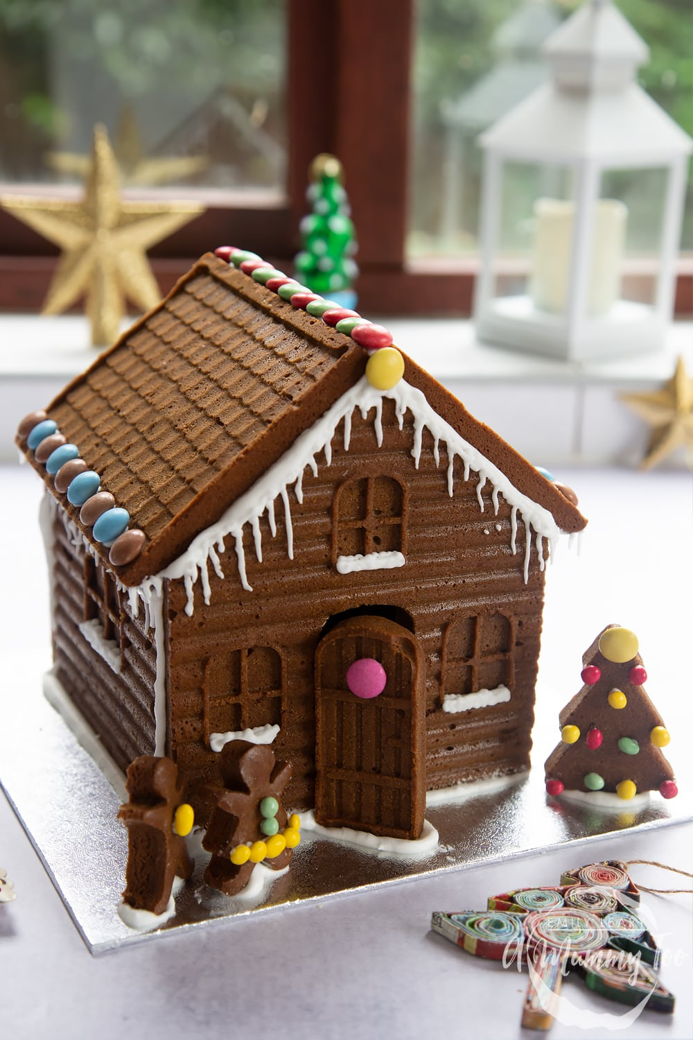 A detailed gingerbread house on a silver board. The house is decorated with smarties and mini chocolate beans, as well as royal icing to resemble snow and icicles.