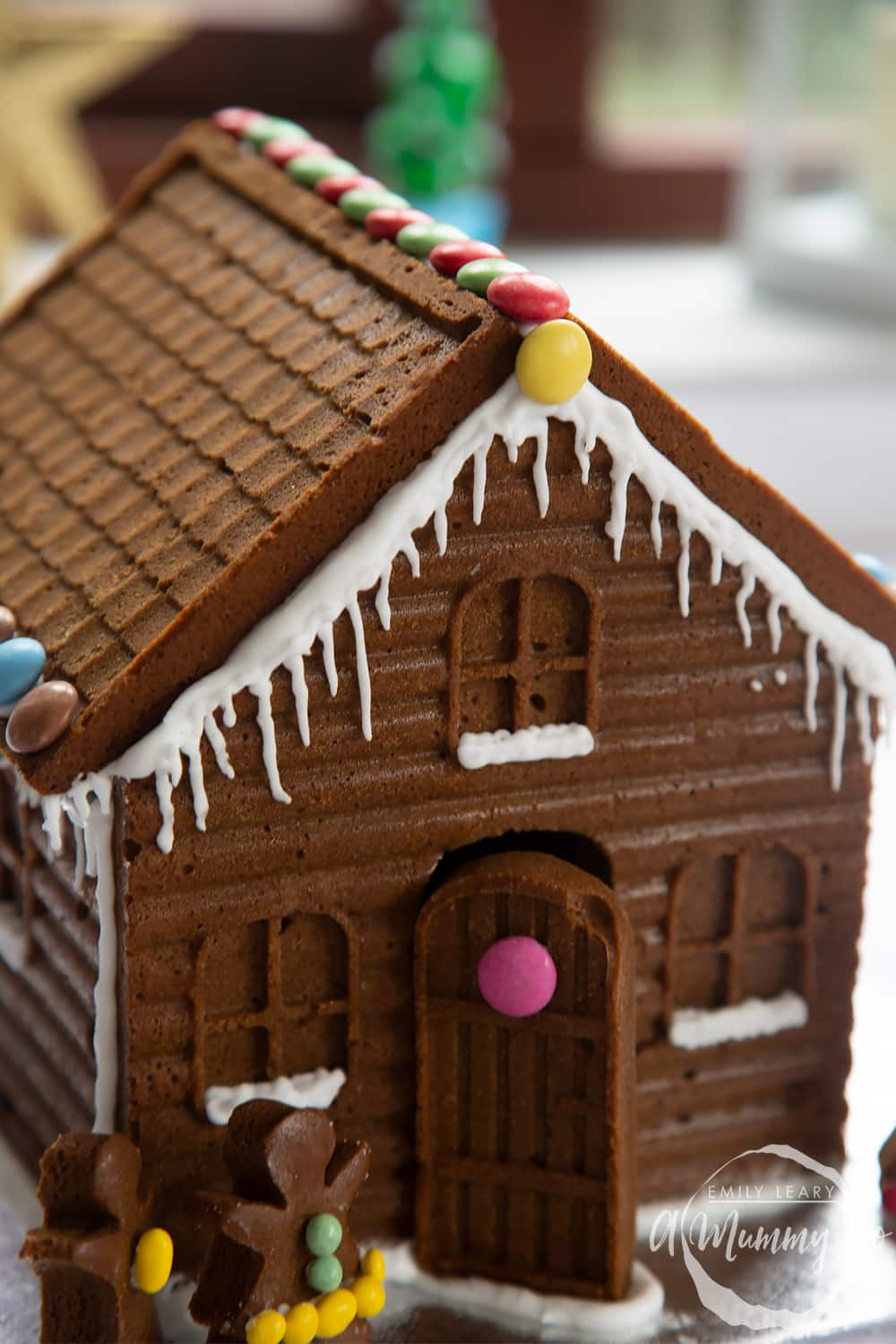 A close up of a detailed gingerbread house on a silver board. Royal icing has been piped along the edges of the roof to resemble snow and icicles.