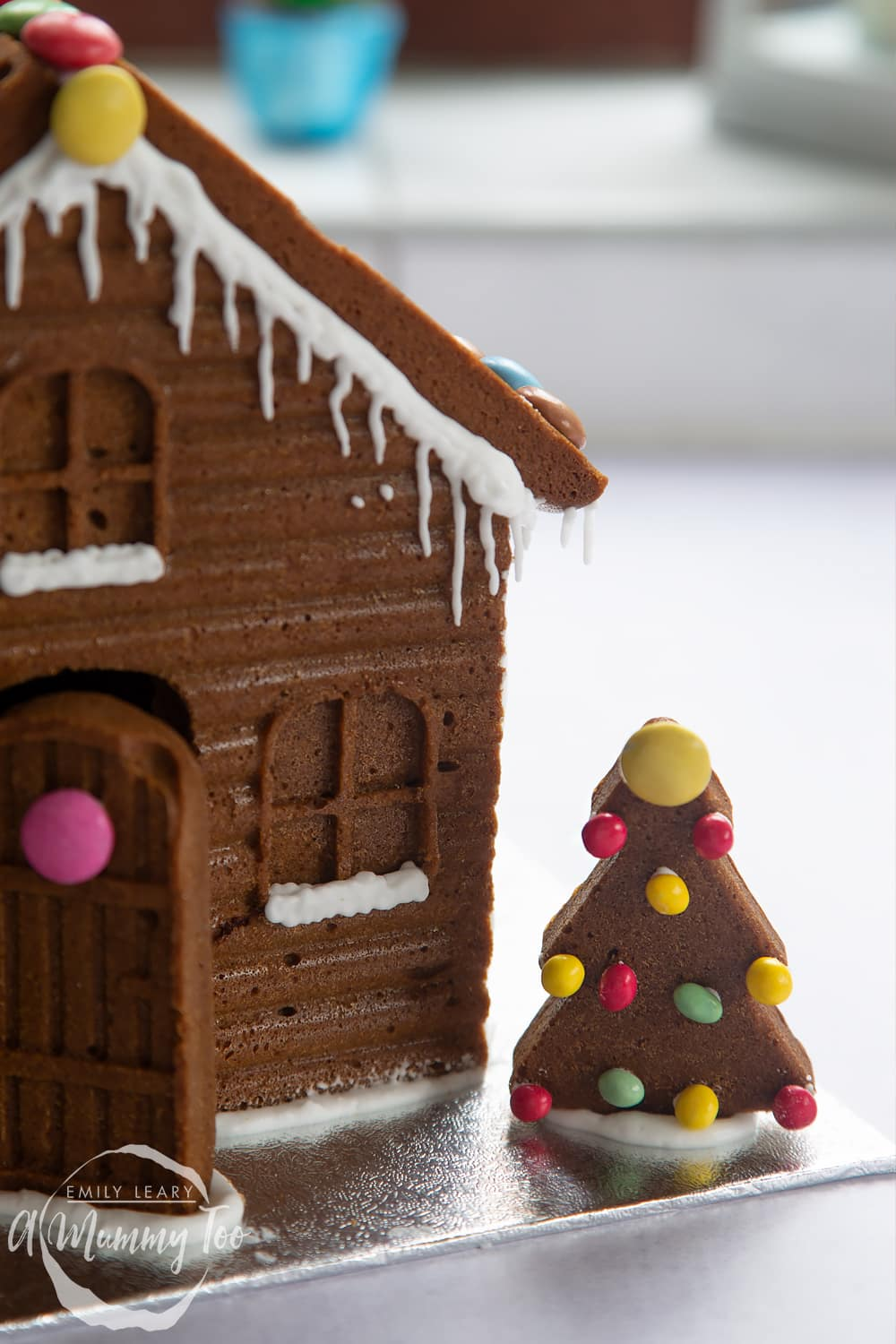 A gingerbread house in close up. The focus is on a gingerbread Christmas tree, decorated with mini chocolate beans.