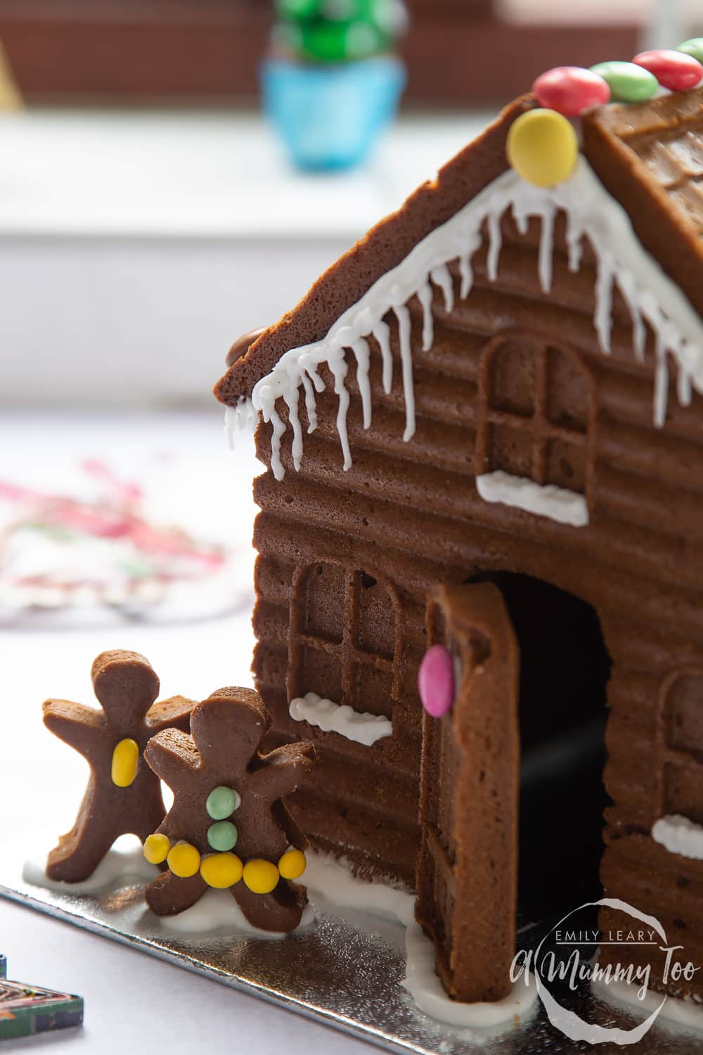 A gingerbread house in close up. The focus is on two gingerbread people, decorated with mini chocolate beans.