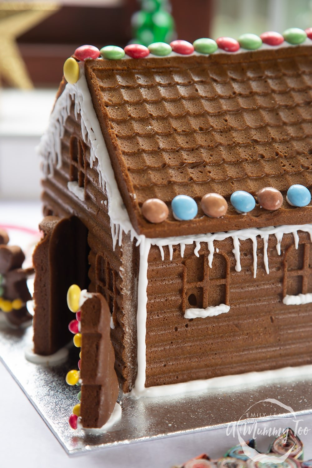 A gingerbread house stands on a silver board. The sills of the windows have been piped with royal icing to resemble snow.