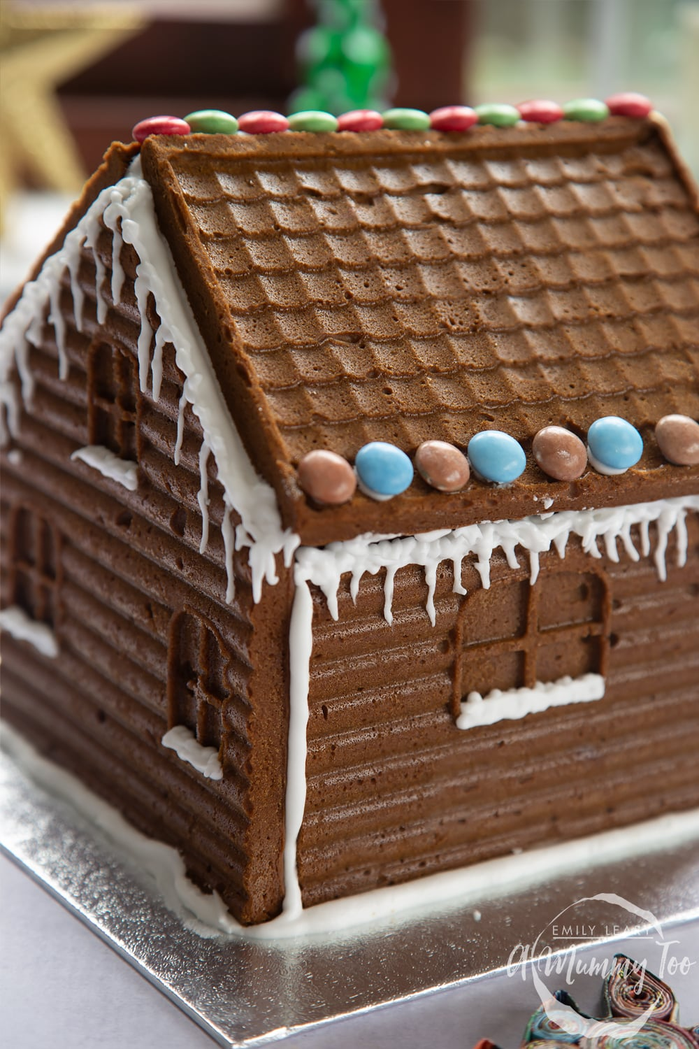 A gingerbread house stands on a silver board. The sills of the windows have been piped with royal icing to resemble snow, while icing icicles hang from the roof, which is also decorated with chocolate beans.