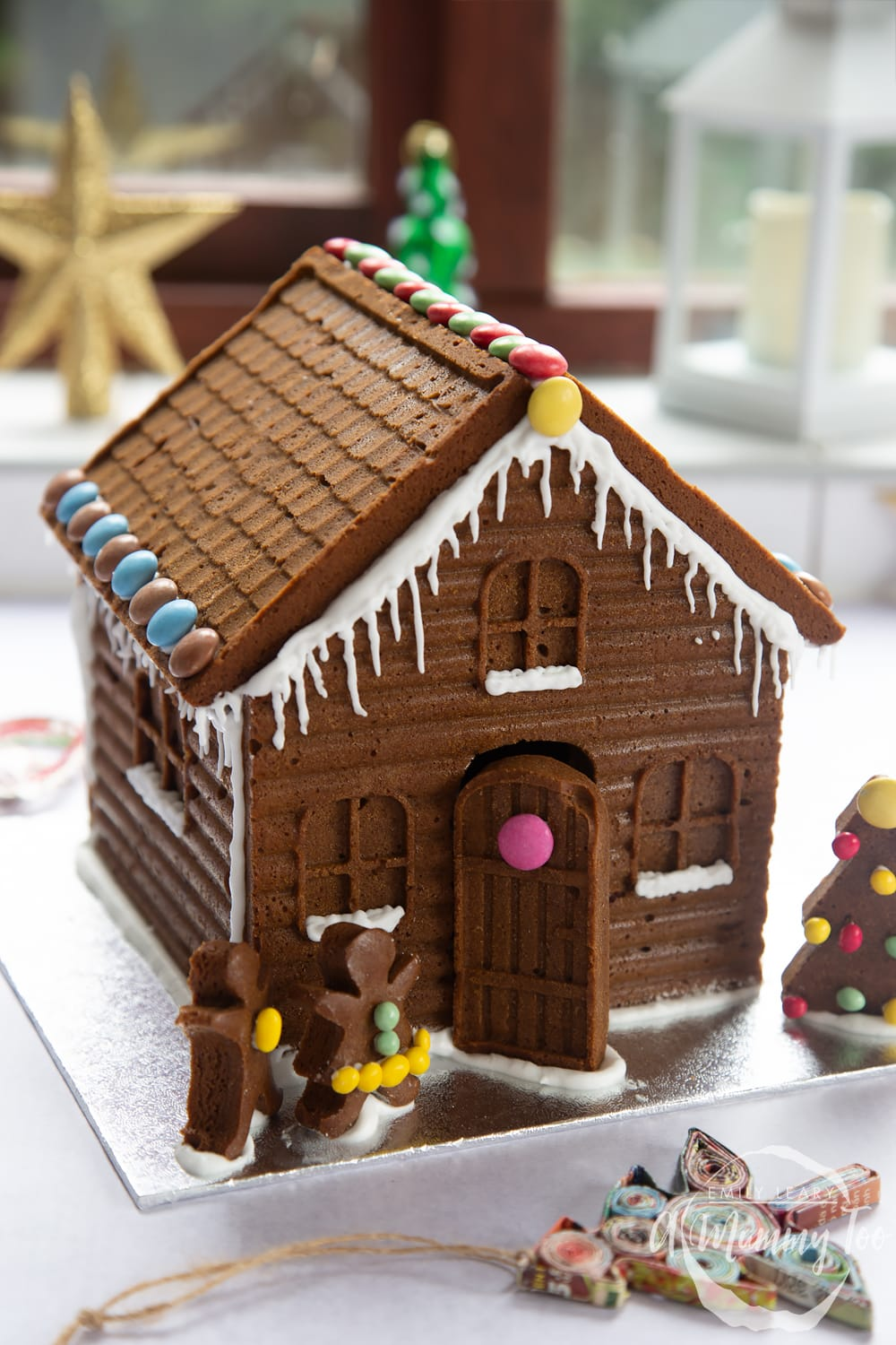 A detailed gingerbread house on a silver board. The house is decorated with smarties and mini chocolate beans.
