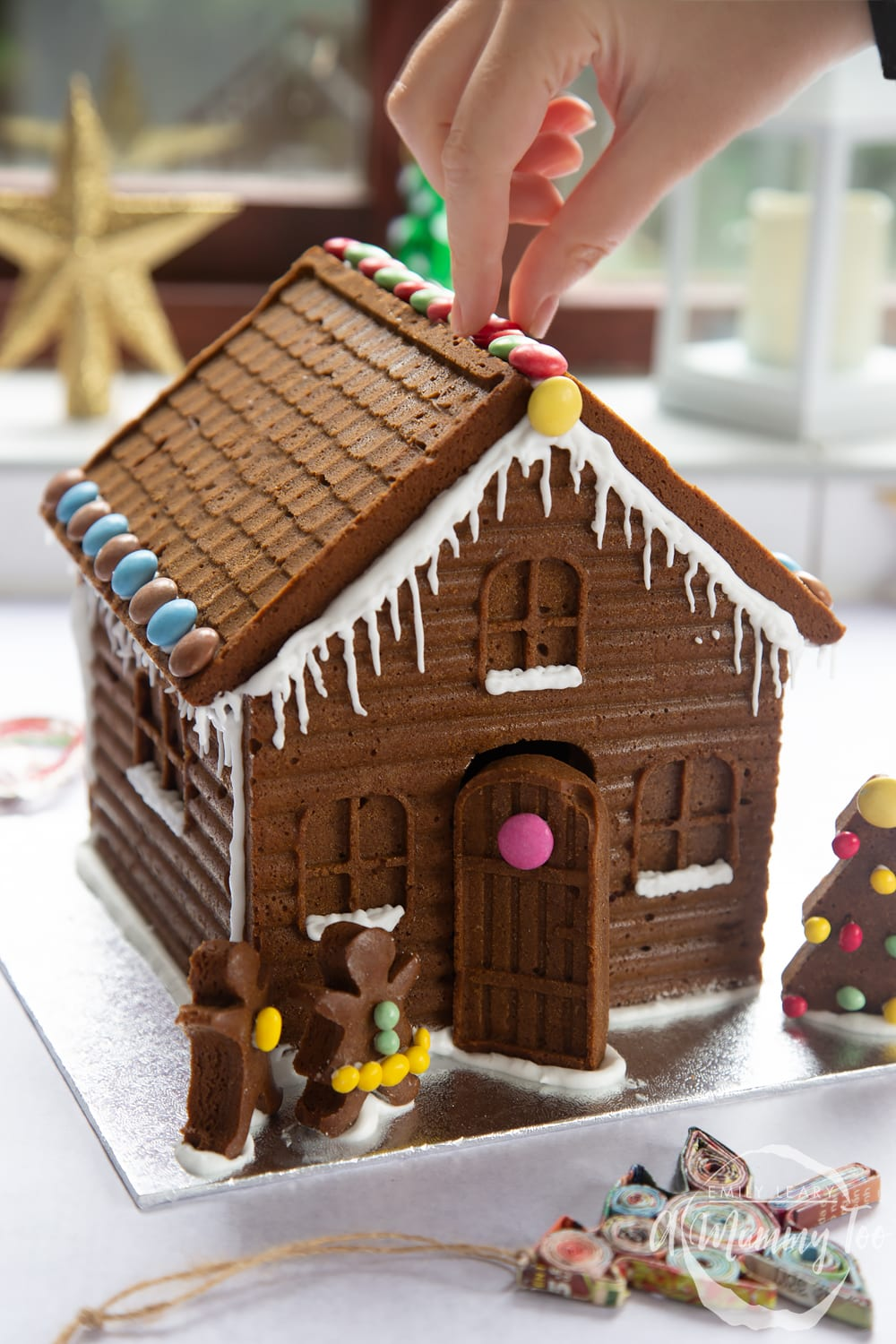 A detailed gingerbread house on a silver board. A hand is reaching in, positioning chocolate beans on the roof of the house.