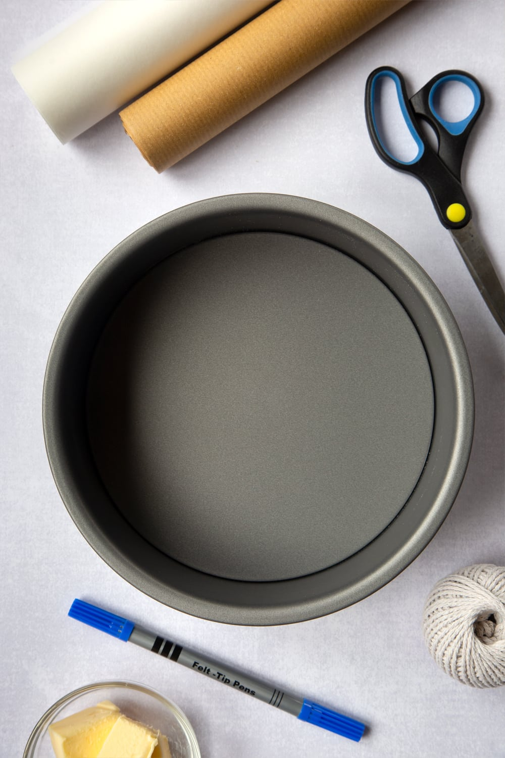 The materials you will need to complete this Idiot's guide to lining a Christmas cake tin. Baking paper, Brown paper, String (non-plastic) A medium loose-bottomed cake tin, Butter (to grease), Scissors, Pen / pencil