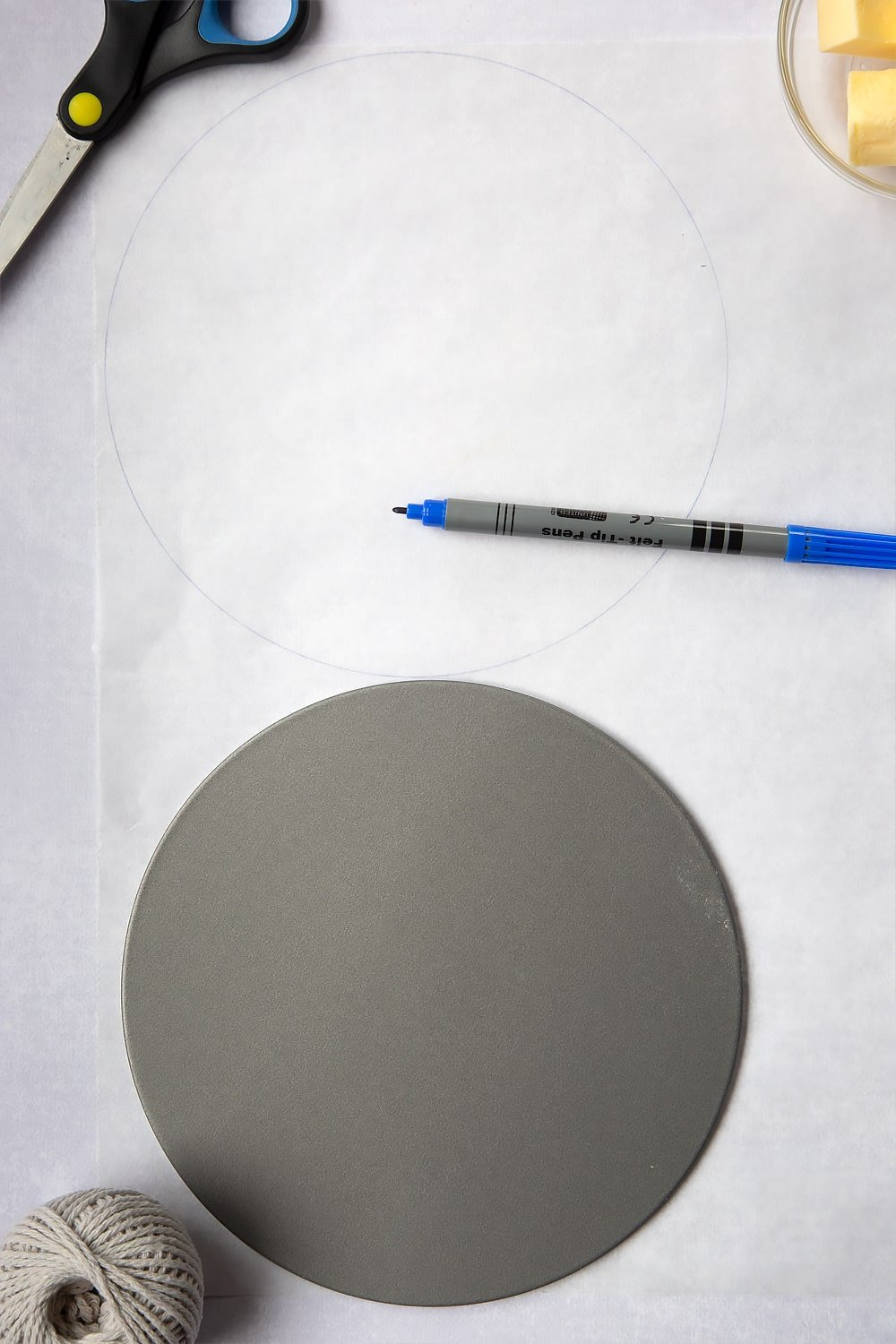 The first step in How to line a Christmas cake tin. An image of a circle which has been drawn by a pen around the cake tin.