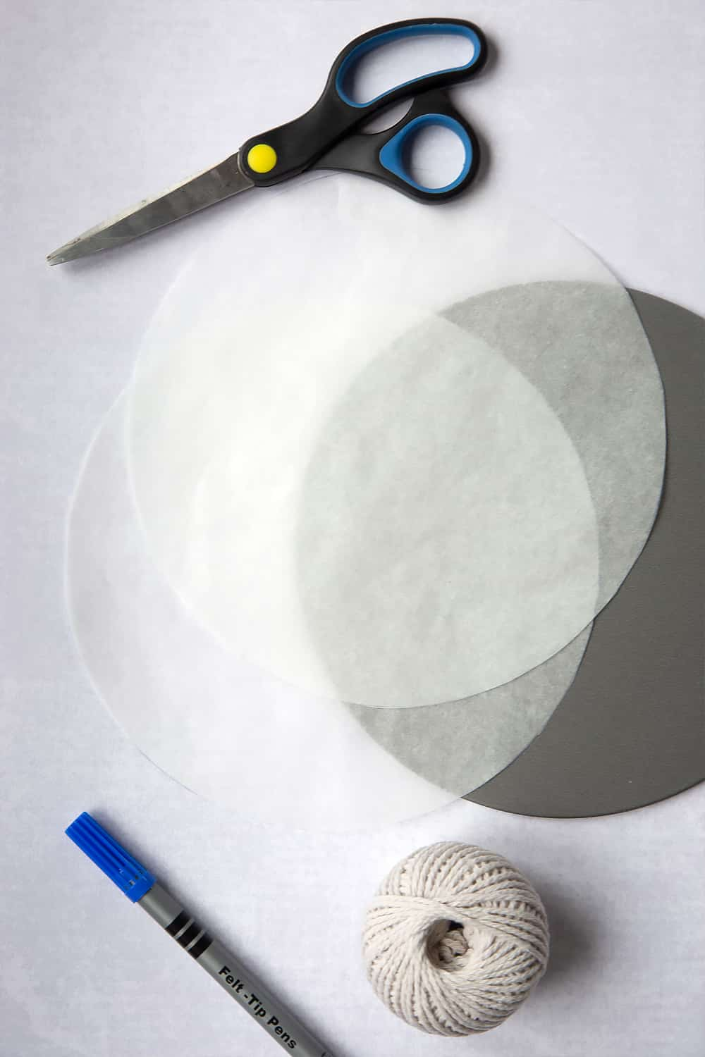 Two circles cut out using scissors from the circle previously made with a pen in step one of How to line a Christmas cake tin.