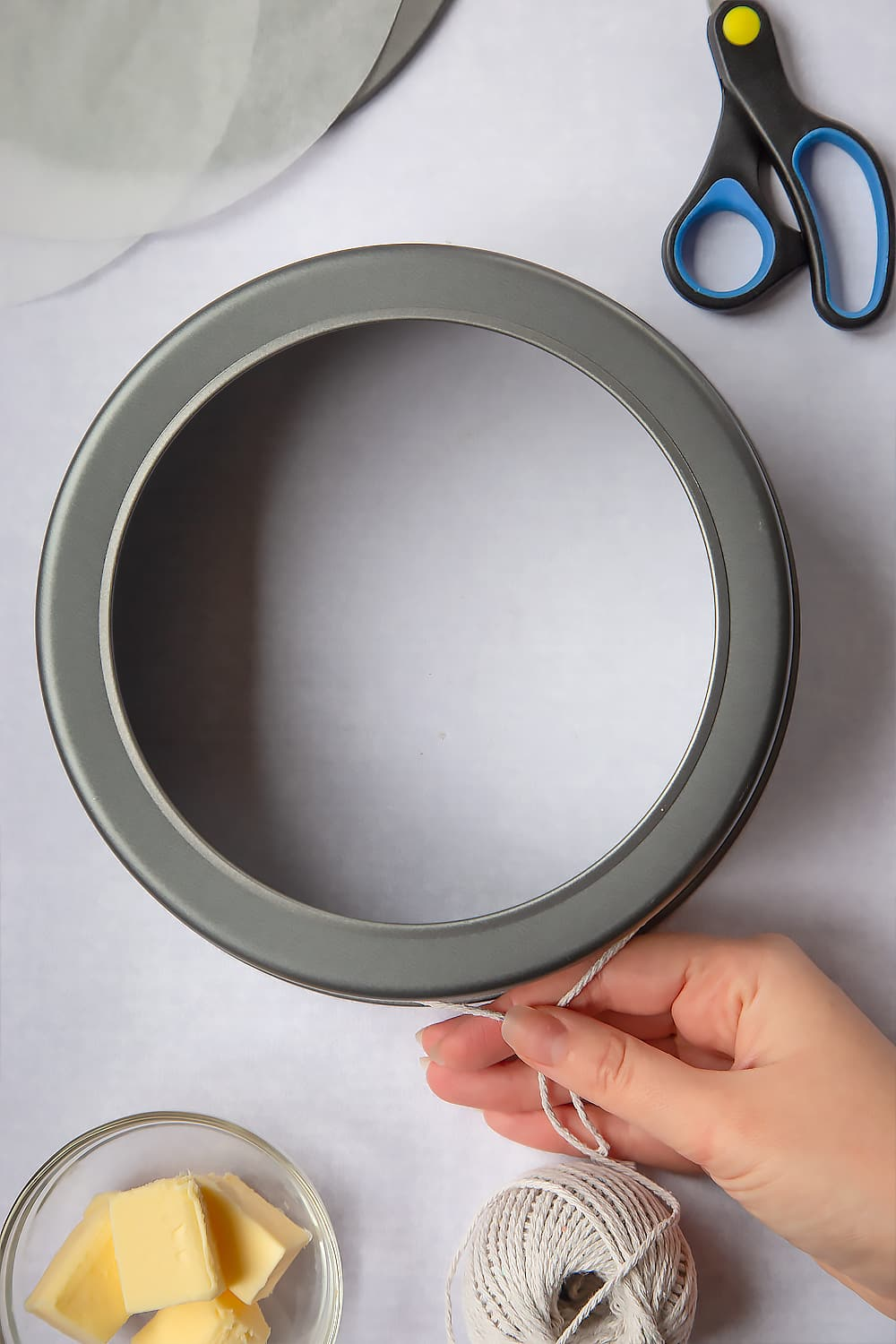 Measuring the inner lining of the cake tin using string (non-plastic) which will be cut using the scissors displayed at the side of the image.